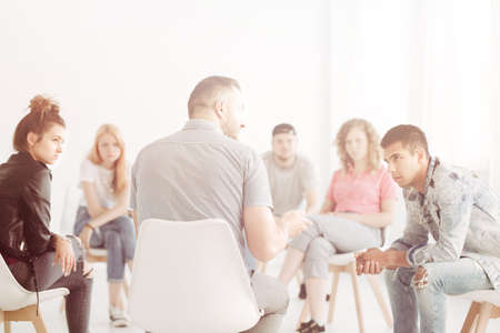 Professional Therapist with group of rebellious teenagers during psychotherapy session