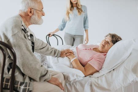 Older man sitting by his sick wife's bed in the hospital Stock fotó