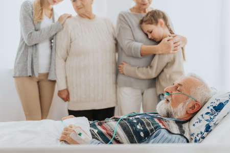 Senior terminally ill man dying in the hospital surrounded by loving family Stock fotó