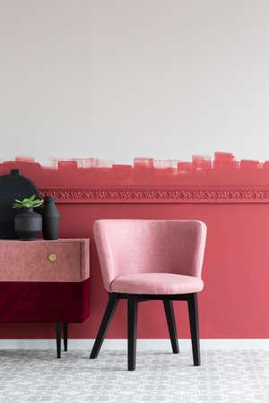 Green flower in black pot nest to black vase on stylish velvet commode next to pastel pink chair Stock fotó