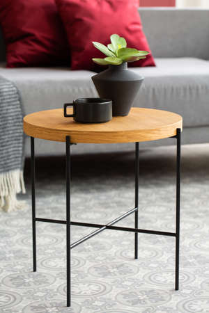 Green flowers in black vase next to black coffee cup on wooden coffee table in stylish interior Stock fotó