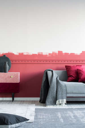 Trendy living room interior with stylish furniture and burgundy wall Stock fotó