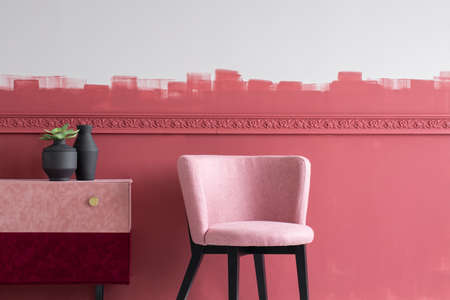 Stylish small pastel pink chair next to trendy pink and burgundy commode Stock fotó