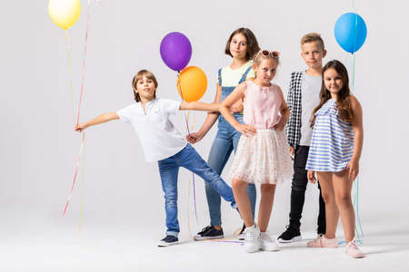 Group of happy children is standing together in a white room and holding colorful balloons Stock fotó