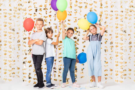 Group of cute teenage boys and girls is standing together in a room and holding colorful balloons Stock fotó