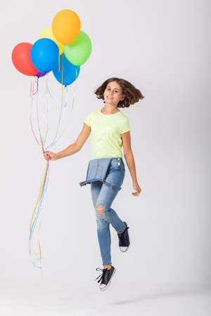 Sweet teenage girl holding a bunch of balloons jumps in an empty room, copy space on the empty wall