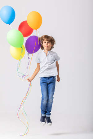 Cool teenage boy holding a bunch of balloons jumps in an empty room