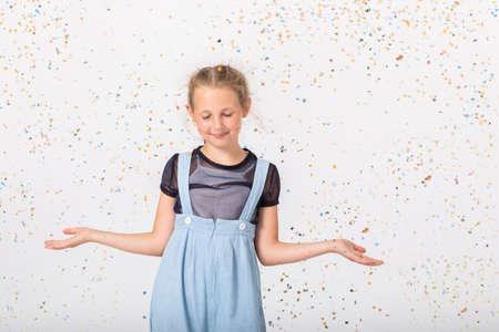 Pretty schoolgirl in blue dress making funny poses, copy space in empty room Stock fotó