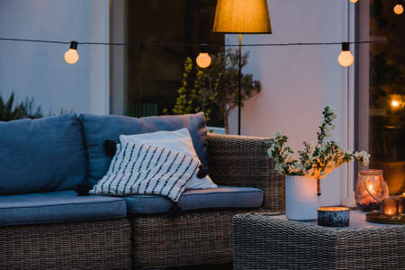 Summer evening on the terrace of beautiful suburban house with patio with wicker furniture and lights Stock fotó