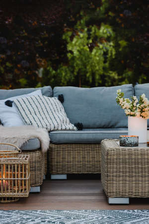 Wicker coffee table and sofa with pillows on the patio of beautiful garden