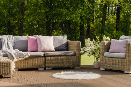 Cozy wooden terrace with gray sofa with pastel pink pillows and blanket Stock fotó