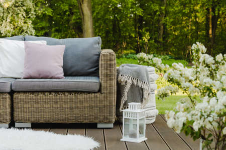 Elegant and trendy terrace with wicker sofa with pillows and blanket in the basket