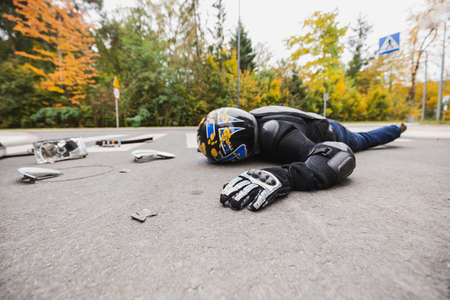 Injured motorcycle driver lying unconscious on the street