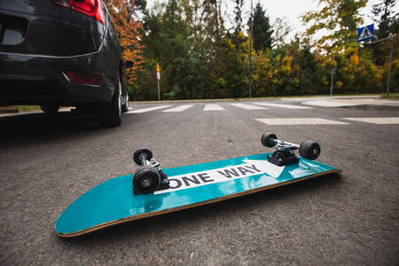 Flipped over skateboard on the road after the accident Stock fotó