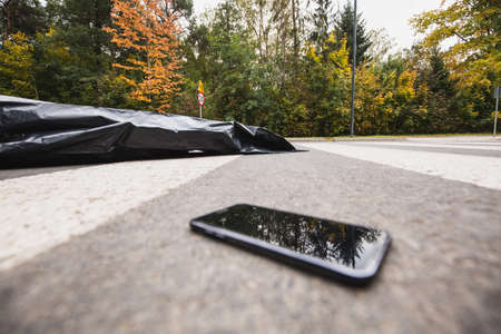 Phone on the street next to the dead body in a bag Stock fotó