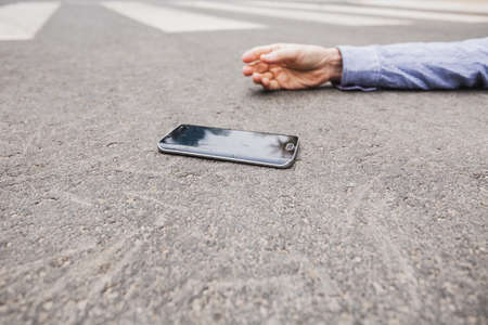 Inattentive pedestrian with phone it by a car Stock fotó