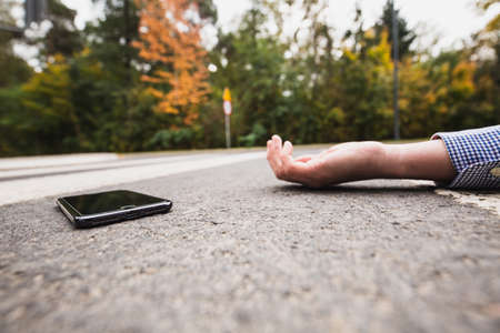 Phone laying on the street next to the unconscious owner
