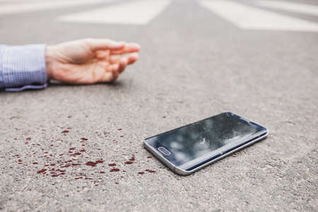 Unconscious pedestrian with phone lying on the road in blood