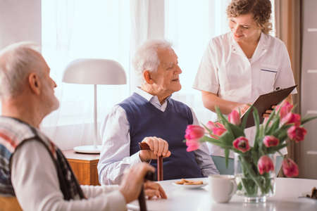 Older man with walking sick talking to a caregiver in a nursing home Stock fotó