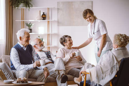 Young helpful nurse taking care of older people in the nursing house Stock fotó