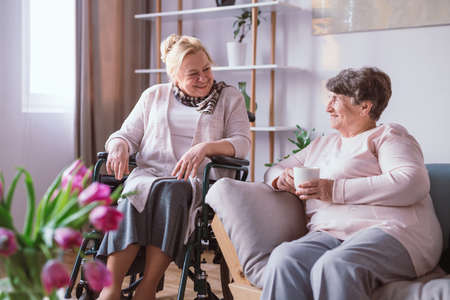 Two older women in nursing home resting together on a couch in the living room Stock fotó