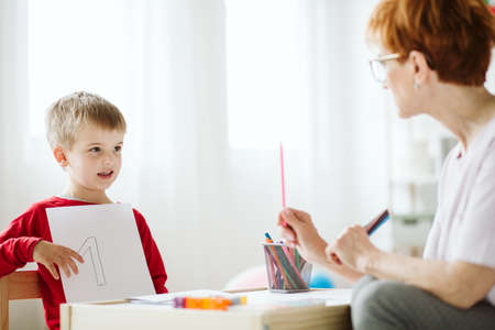 School therapist and young autistic boy learning the number on individual classes Stock fotó
