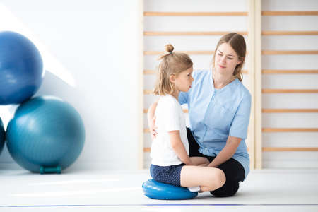 Cute little blond girl exercising with her professional physician