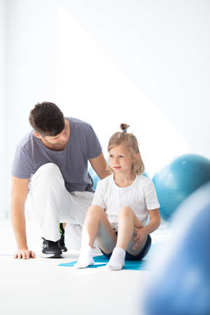 Cute blond girl sitting on the yoga mat, helpful trainer next to her Stock fotó
