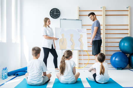 Trainer and nurse explaining to small children types of spine problems