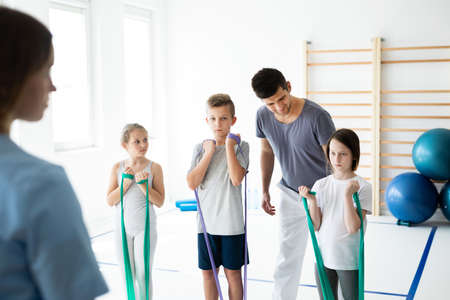 Kids exercising with tapes, helpful trainer standing behind them