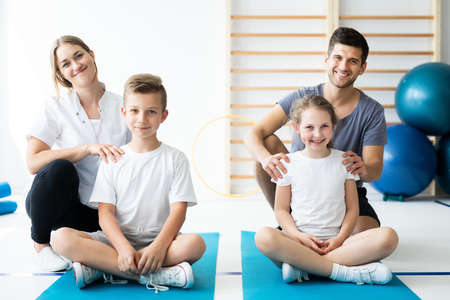 Kids sitting on blue yoga mats with their professional physician Stock fotó
