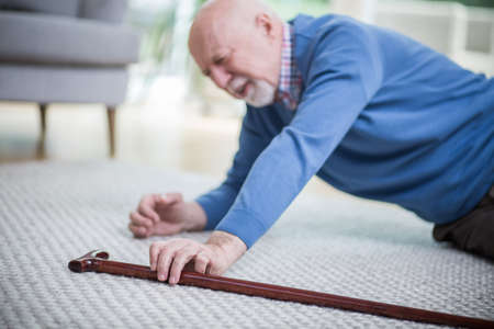 Senior man in blue sweater lying on the floor of his apartment