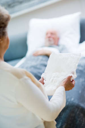 Senior wife stands in front of the bed of her sick husband and holds an adult diaper