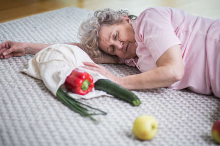 Old lady lying on the floor next to shopping bag with vegetables