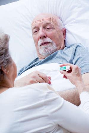 Elderly wife measures the temperature of her sick husband lying in bed Stock fotó