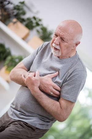 Senior gray man home alone having a heart attack