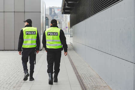 Two police officers in reflective vests patrol the streets of the city