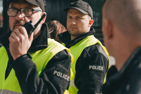 Close up of policemen speaking on the walkie-talkie during intervention