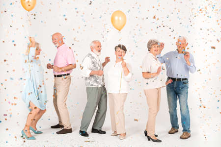 A group of elegantly dressed elderly people standing in a white room