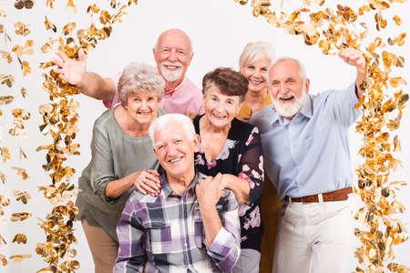 Happy group of senior friends looking through a curtain of golden decorations Stock fotó