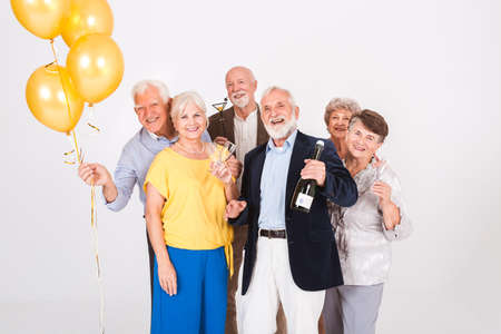 Group of happy senior friends holding yellow balloons and standing in white interior