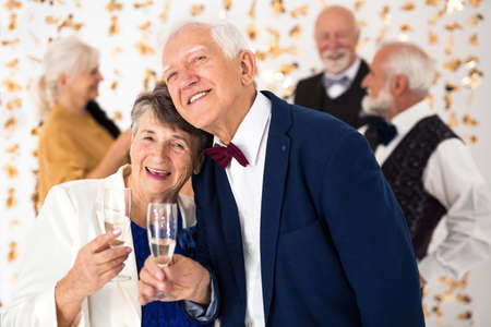 Cute elegant senior couple toasting with champagne during New Year's Eve