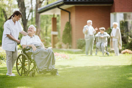 Walking with disabled man in the nursing home garden