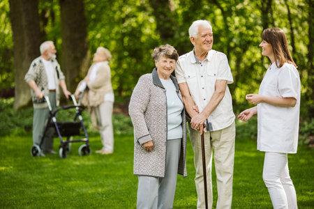 Elder people with the caregiver in the garden Stock fotó