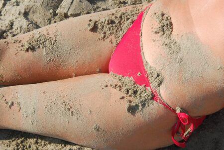 parte: Parte di corpo di ragazza in costume rosso con sabbia sulla pelle Stock Photo