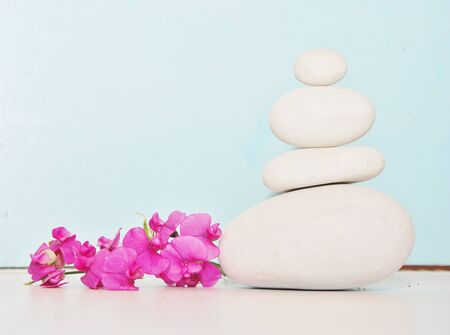 stacked white stones and flower fuchsia, light blue background photo