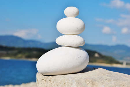 round white stones stacked in the background lake photo