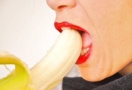 young woman shows and eats banana in a provocative way Stock Photo - 17980273