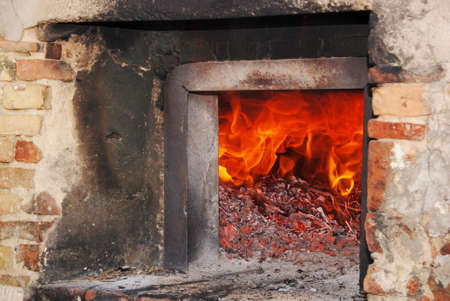 to get warm: flames and glowing embers in the wood oven Stock Photo