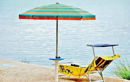 placidity: umbrellas and lounge chairs on the beach of Lake Trasimeno, Italy Stock Photo